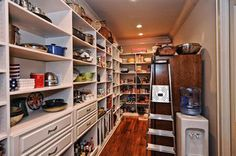 walk in pantry with fridge for extra storage and bottled water unit out of sight of the kitchen