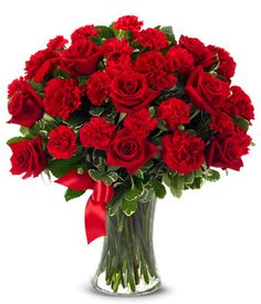 """Red Heart  $73.99   Red roses and red carnations convey heartfelt emotions, accented by a vivid red ribbon and superbly arranged in a clear gathering vase. Arrangement measures 17""""H by 15""""L."""
