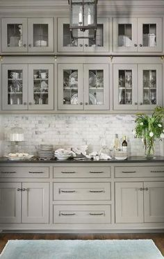 Light gray butler pantry features glass front cabinets with black hardware over . Light gray butler pantry features glass front cabinets with black hardware over Carrera marble mini brick tiles creating a stunning backsplash. Backsplash For White Cabinets, Glass Front Cabinets, Dark Countertops, Dark Cabinets, Backsplash Tile, Kitchen With Black Countertops, Glass Kitchen Cabinets, Light Gray Cabinets, Laminate Countertops