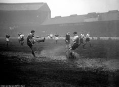 In a cloud of spray Chelsea's Peter Brabrook smashes the ball straight at Bolton's Ralph Gubbins