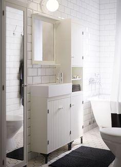 Et hvidt badeværelse med et smalt skab til vask, højskab og spejlskab