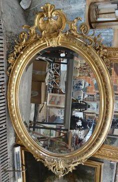 Miroir ovale en bois stuqué sculpté doré et ajouré de rocailles