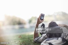 Stockfoto : Young man lying on grass in park selecting music on smartphone