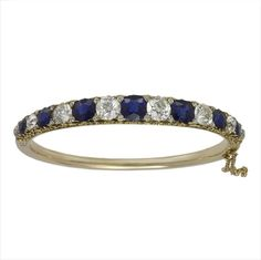 A VICTORIAN SAPPHIRE AND DIAMOND GOLD HALF HOOP BANGLE, the seven oval faceted sapphires weighing a total of 8.27cts alternately-set between eight old brilliant-cut diamonds weighing a total of 6.06cts, all in a gold carved half hoop setting embelished with rose-cut diamonds to a plain gold back hoop and fitted safety chain, gross weight 21.8 grams, circa 1870.