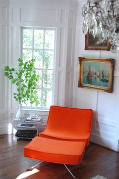 Old art, white walls and tangerine chair