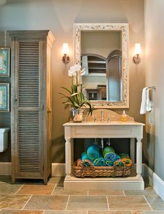 This open vanity includes a shelf for a basket to store towels in, and the shape of its backsplash gives it vintage appeal. A stand-alone cabinet separates the toilet from the vanity and allows for additional storage.
