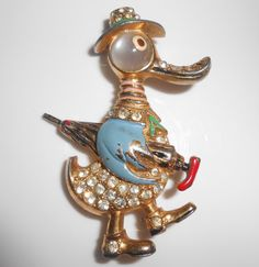 Duck Figural Brooch Pin 1940s Enamel Rhinestone Pin. Measures 2 1/4 long and 1 1/2 at widest point. Gold tone metal, enamel and clear rhinestones. Faux moonstone eye, all stone present with a couple showing wear, obvious enamel and metal wear age appropriate. Lovely whimsical piece.
