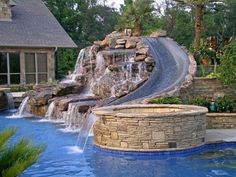 Hours and hours of fun with friends, kids and the whole family await the owner of this spectacular backyard oasis. The slide winds down the backside of the pool and provide a big splash landing. Love the water spilling over the entire structure. From our blog post Cool Pools You Can Dip Your Toes Into. See more by clicking on photo