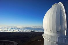 View Larger  The view is spectacular from the 14,000 ft. (4,200 meter) summit of Mauna Kea, on the island of Hawaii.  Seen here is the Canada-France-Hawaii Observatory, housing a 3.6 meter optical telescope.  There are 12 other telescopes nearby, owned by different countries and academic institutions.  The summit of Mauna Kea is well above a dramatic looking inversion layer of clouds, which keeps the moist marine air below.  It is so dry here that my kite fabric had shrunk, making the kite…