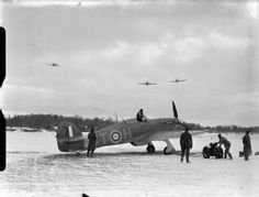Squadron Leader R R Stanford Tuck, Commanding Officer of No. 257 Squadron RAF, in his Hawker Hurricane Mark I, V6864 'DT-A', prepares to lead a section of Hurricanes to their take-off point, in the snow at Coltishall, Norfolk.