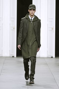 Dior Homme Fall Winter 2012-2013 – Look 10: Officer green wool and cashmere flannel two-button suit, narrow lapel suit jacket, soft pant, officer green herringbone-knit zippered alpaca coat, white cotton poplin button-down collar shirt, officer green cotton jersey short-sleeved, raised neck t-shirt, officer green wool and cashmere flannel cap, officer green wool and silk panama tie, beige linen lining and trim, black grained and smooth leather Chelsea boots. Discover more on www.dior.com