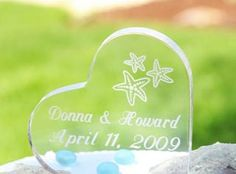 "Beautifully crafted with sturdy acrylic, Heart Shaped Cake Topper with starfish offers a perfect finishing touch to your beach themed wedding cake. Starfish topper measures 4"" x 4""x 1.5"" thick and is the perfect keepsake of your wedding day. Personalization is available with first names and wedding date at no additional charge (maximum 24 characters per line). Also available in square and round shaped with etched starfish design."