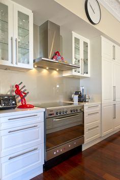 Crisp white kitchen with stainless steel appliances and classic clean lines offset by the warmth of jarrah floorboards.