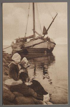 Twee meisjes op de dijk met hul, katoenen jak en donker schort met geruit bovenstukje. De turfschuit, een tjalk, wordt gelost op de achtergrond. 1900-1925 #NoordHolland #Volendam