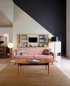 tapis sisal, un haut plafond, sofa rose, table en bois