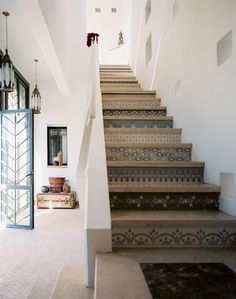 The handcrafted chevron-patterned doors were designed by Montague and Redecke, and the stenciled stair risers are the creations of Melanie Royals of Royal Design Studio.
