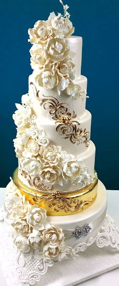 Cascading Floral Bouquets with a Golden Tier Wedding Cake