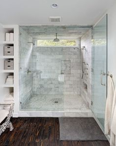 Master bath features walk-in shower accented with white marble subway tile surround framing window alongside rain shower head, marble shower niches and marble hex shower floor.: