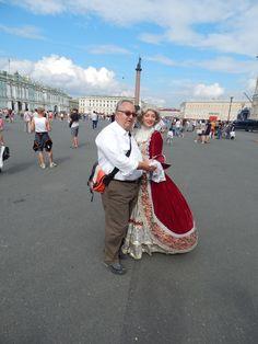 Ein Gast mit einer Puppe auf dem Palastplatz vor der Eremitage.
