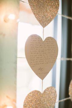 heart cutouts of love letters between the bride and groom, photo by Hot Metal Studio http://ruffledblog.com/white-barn-wedding #weddingideas #garlands
