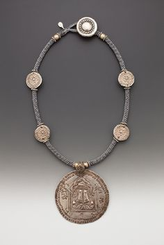 by Tamara Hill | Round antique Indian embossed silver Vishnu Pada 'Patvi' (feet) pendant', embossed silver Turkoman discs, 'wheel' spacers, Ethiopian silver beads 12-strand crown knotted cord, vintage embossed silver metal button.   {Price not published, contact seller}