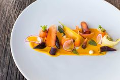 """Carrots Four Ways - Underbelly, Houston - Chef Chris Shepherd has one rule: Never say no to a farmer. So when he gets a bulk of carrots, he will figure out what to do with them. These days, he pickles, blanches, shaves, and purees them. But by tomorrow, he may roast them in a coffee rub or burn them to a marshmallow-like pulp. No matter what, his fun-loving, """"T'hell with it"""" style always ends up in a pretty plate."""