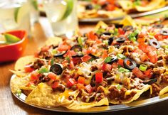 Crisp tortilla chips are layered with classic taco seasoned ground beef, cheese, tomatoes, olives and onion, then baked until piping hot to make this fun and flavorful appetizer in just 30 minutes!