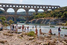 Les visiteurs du Pont du Gard se baignant sur la plage en rive droite du site pour LES RENDEZ-VOUS À LA RIVIÈRE. Photo : Y. de Fareins