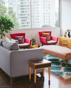 Poltroninhas coloridas e um tapete estampado fazem a diferença nessa sala iluminada com sofá cinza.