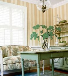 Striped wall covering & white shutters subdue sofa fabric while distressed painted furnishings give interest in country style room