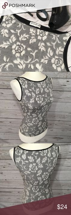 """Bebe stretch silvery gray & black brocade top •Details• Very stretchy floral pattern brocade sleeveless top with black trim. Size tag is missing so measurements are provided below. It should fit small to medium. •Condition• Excellent gently used condition  •Material• 75% nylon 25% Lycra •Color• Black & silver gray All measurements taken while item is laying flat & are approximate •Armpit to Armpit• 16"""" stretching to 19"""" •Length• 19"""" bebe Tops"""