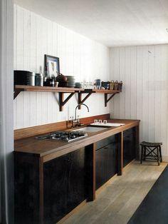 Walnut work top, black cupboards, open shelving.