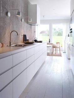 Betonnen achterwand is mooi contrast met strakke keuken.