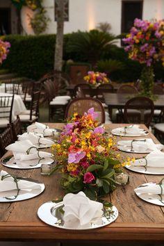 Decoração de casamento colorida em tons de rosa,laranja, amarelo e lilás. Mesa rústica em madeira, sousplat de prata na Fazenda Capoava