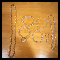 Pearl necklaces, bracelets, and earrings 2 pearl necklaces, 4 pearl bracelets, and a pair of pearl earrings. Note that all pearls are plastic, and pearl bracelets are elastic. Longer pearl necklace is a pale pink, all others are white. Jewelry Necklaces