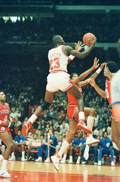 Michael Jordan attacks the rim before Dr. J gets to him.