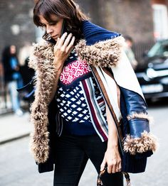 A shearling jacket is paired with a mixed print sweater, black jeans, and a Gucci bag