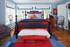 An antique red dresser and weathered shutters set the color scheme for this bedroom. Windows are a dramatic backdrop for Ethan Allen's Quincy bed, with Roman shades from The Shade Store. The dusty blues and greys add a light-reflective quality to the room and the ideal compliment to the brighter touches in the duvet, blanket, and pillows.