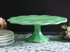 Gorgeous light green Jadeite cake stand. Made using vintage Fenton molds, this cake stand is possibly a Martha Stewart by Mail piece, but it is not marked, so I cannot be sure. Ive done some research, and found that not all of the Martha cake stands were marked. If you collect and use vintage Jadeite this piece will blend right in. This pretty cake stand has a scalloped edge on the cake plate and on the fluted pedestal base. Beautiful swirls of color variation are visible on the top of the…