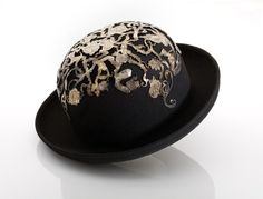 Hat | Made in Great Britain by Atelier, 1989 | Materials: wool felt with applied silver-plated brass decoration, pierced and embossed | Atelier was established in 1984 by Julian Brogden, and originally specialised in jewellery. In 1986, Cathi Jordan became a partner in the business. They collaborated together to create inventive jewellery, accessories, and by the late 1980s, unusual headwear such as this bowler overlaid with a tracery of silver-plated brass | VA Museum, London