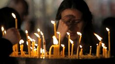 A woman crosses herself after lighting a candle during Easter service at St. Easter Service, Christian World, Votive Candles, Christianity, Concert, Celebrities, Crosses, Sunday, Facebook