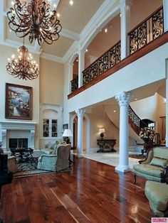 Large open main room with pillars, wrought iron and chandler. Oh and wood floors. And fireplace. The stair case and hall looking into living room is exactly what I want. This is all so so perfect