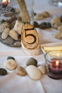River rock table numbers with mason jars and wildflowers
