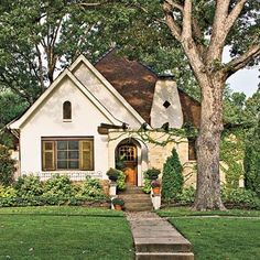 cream exterior, pergola on front, front porch, brown roof