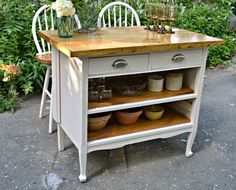 Repurposed antique dresser as a kitchen island with a butcher block