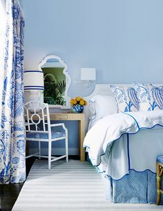 Bedroom with blue walls, blue print curtains, desk as nightstand, Chinese Chippendale white rattan bamboo chair, striped rug, pleated bedskirt, white headboard, rattan bench.