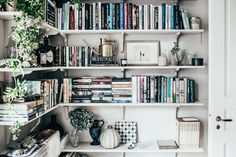 Open white shelving in living room are a lovely use for books, styling and indoor plants. Photo Kristin Lagerqvist