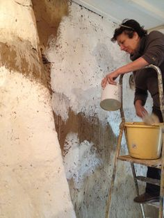 In France painting on my freshly 'plastered'  mud walls of my French house.   Using Old White watered down and applied over the mud which I have wetted before applying the paint so it absorbs in.