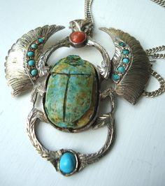 Egyptian Revival Scarab Necklace. Scarabs are associated with the Egyptian god, Khepri. It was Khepri that pushed the sun across the sky. The scarab beetle became an ancient Egyptian symbol for rebirth, the ability to be reborn. Each day the sun disappeared, always to rise again and be reborn the following day.