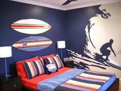 Bedroom: Surfer Wall Mural For Boy Bedroom. beach themed room. surf themed bedroom. room decor for boys. red bedding. surfing board decor. striped blanked. white lamp shade. dark nightstand.